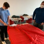 Students cutting cloth for a no sew blanket
